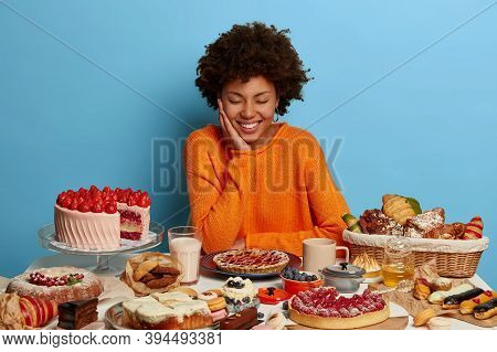 Positive Afro American Woman In Orange Jumper Sits At Festive Table, Surrounded With Many Desserts,