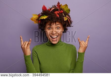 Yeah, Its Cool. Overjoyed Woman With Afro Hair Decorated By Colorful Leaves, Enjoys Autumn Time, Rai