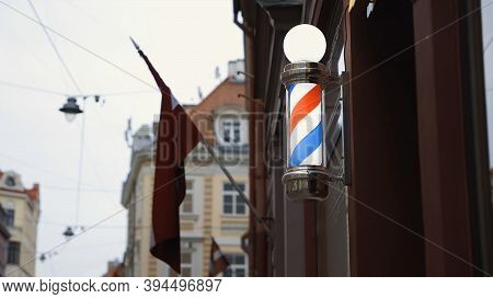 Bright Red White Blue Barbershop Pole On Wall With Lv Flag In Background