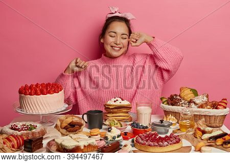 Happy Asian Birthday Girl Comes On Tea Party, Eats Sweet Delicious Cakes, Streches Hands With Enjoym