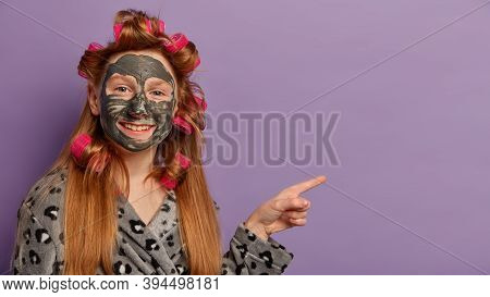 Horizontal Shot Of Cheerful Girl Has Toothy Smile, Applies Clay Mask For Healthy Complexion, Wears C