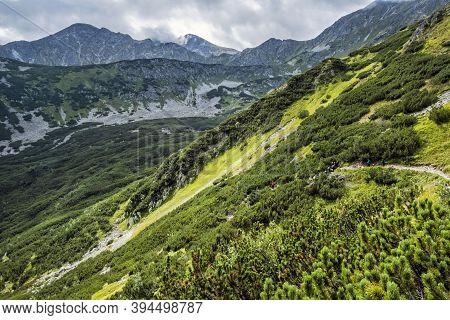 Tourists In Western Tatras Mountains, Slovak Republic. Hiking Theme. Seasonal Natural Scene.