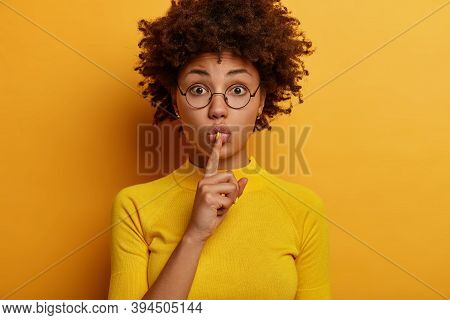 Headshot Of Secret Dark Skinned Woman Has Surprised Expression, Presses Index Fingers To Lips, Hides