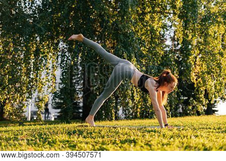 Side View Of Flexible Young Woman Practicing Yoga In Down Facing Dog Pose On One Leg, City Park At S