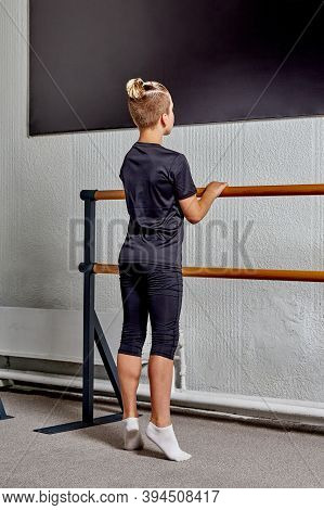 A Sporty Young Man Stands With His Back To The Bar And Trains To Learn Ballet.