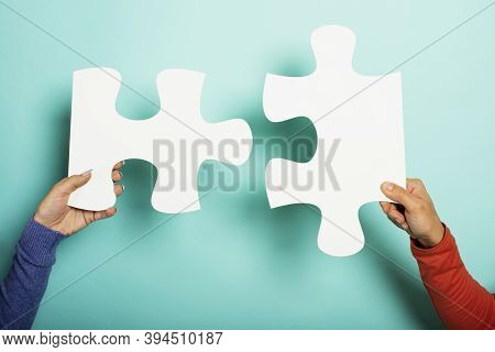 Two Peoples Join Piace Of Puzzle. Concept Teamwork, Partnership, Integration. Cyan Background