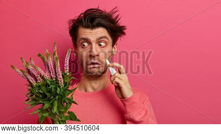 Horizontal Shot Of Puzzled European Man Uses Nasal Drops, Has Seasonal Allergy, Reaction On Trigger,