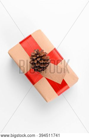 Christmas Gift Tag Mock Up With Gift Box Wrapped In Craft Recycled Paper With Red Ribbon And Pine Co