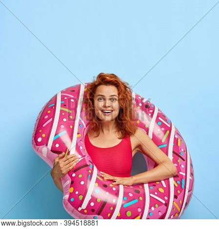 Photo Of Happy Redhaired Woman Dressed In Bikini, Poses With Swimring, Enjoys Summer Vacation, Isola