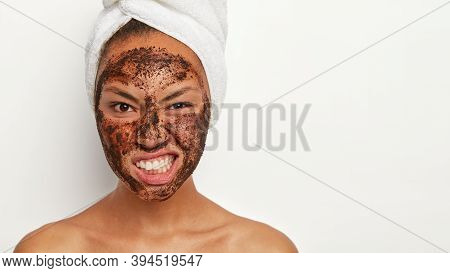 Photo Of Displeased Female Model Smirks Face, Being Dissatisfied With Something, Has Coffee Scrub Ma