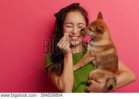 People, Love To Animals Concept. Positive Korean Girl Plays With Shiba Inu Dog, Makes Mini Heart Han