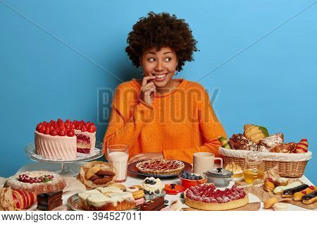 Charming Female Sweet Tooth Looks With Smiles Aside, Thinks About Something While Poses At Birthday