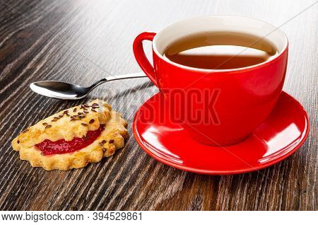 Teaspoon, Shortbread Cookie With Raspberry Jam And Linseeds, Red Cup With Tea On Saucer On Dark Wood