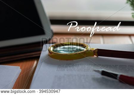 Magnifier On Blurred Proofreading Paper With Proofread Text Floating Above On Wooden Table Nearby Wi