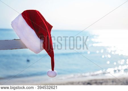 Santas Red Hat On The Sea Background. Tourism During The New Year Holidays. Christmas Decor. Copy Sp