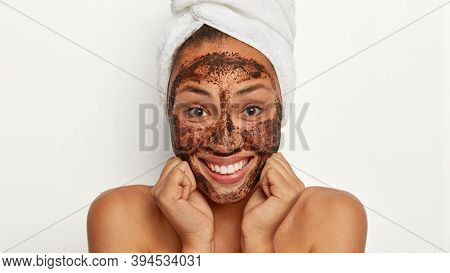 Close Up Shot Of Attractive Woman Keeps Hands Under Chin, Exfoliates Skin With Coffee Scrub, Smiles