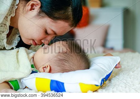 Mom Lay Hugging A Baby Son Asleep On A White Bed.