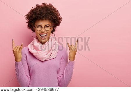 Lively Dark Skinned Young Lady Makes Rock N Roll Or Heavy Metal Gesture, Enjoys Awesome Party, Feels