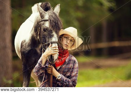 Portrait Of The Young Girl And The Horse. Equestrian Girl. Cowgirl And Her Pony, Close Up