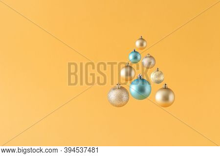 Creative Original Christmas Tree Made Of Gold And Blue Christmas Balls On Yellow Background. Minimal
