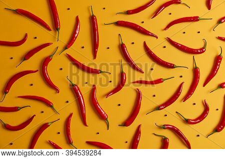 Overhead Shot Of Long Thin Ripe Red Chili Pepper And Black Peppercorns Arranged Around Yellow Studio