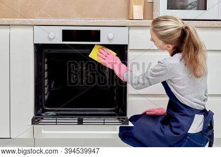 A Young Woman Is Cleaning The Oven In Pink Rubber Gloves, Cleaning The Kitchen.
