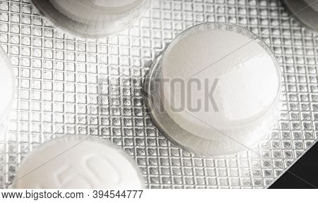 Macro Closeup Perspective View Of Row Medical White Round Pills Protected In Plastic Capsule On Silv