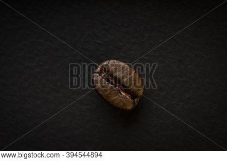 Roasted Dark Coffee Bean Closeup Over Dark Background