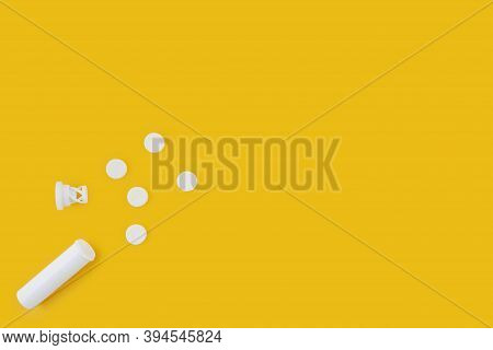 White Vitamine Pills Spread Out Of Round White Box Over Yellow Background