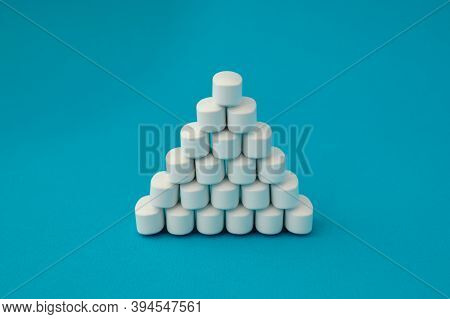 Pharmacology Medical Concept Pyramid Of White Pills Tablets Drugs On Cyan Surface With Copyspace