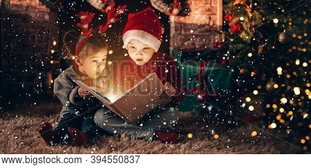Brother And Sister Are Sitting And Reading A Book. Christmas Mood. Children In New Years Costumes Ag