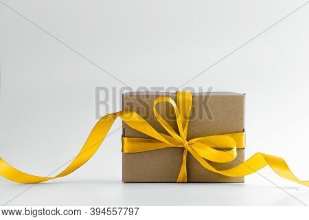 Close-up View Of White Gift Box With Elegant Pink Ribbon In Luxury Bow On Dark Background And Reflec