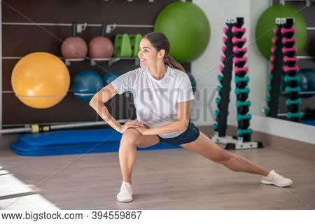 Smiling Dark-haired Female Stretching Legs, Hands On Her Right Knee