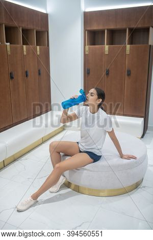 Dark-haired Female Sitting On Pouf In The Changing Room, Drinking Water