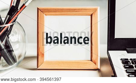 The Word Balance In A Wooden Frame On A Table With A Laptop And Pens. Business Concept.