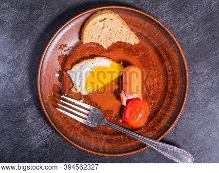 Unfinished Light Quick Breakfast - Fried Egg, Tomatoes, Sausage And A Piece Of Bread On An Clay Plat