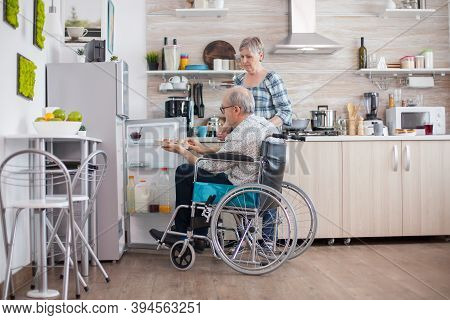 Handicapped Senior Man In Wheelchair Taking Eggs Carton From Refrigerator For Wife In Kitchen. Senio