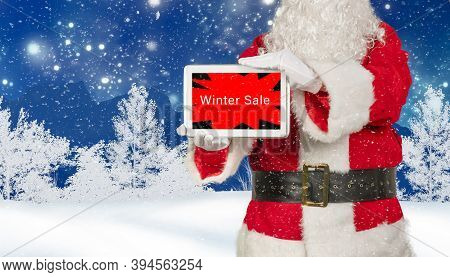 Santa Claus Holds Tablet With Winter Sale Advertising On Wintery Background