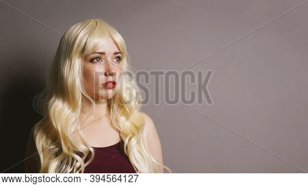 Serious Thoughtful Young Blonde Woman Thinking And Looking To Side Withcopy Space Ongray Background