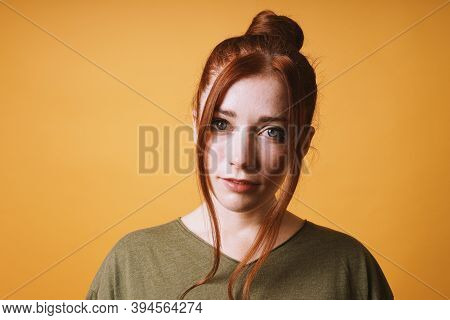 Cool Young Woman With Red Hair Messy Bun Hairstyle And Loose Strands At The Front Against Yellow Ora