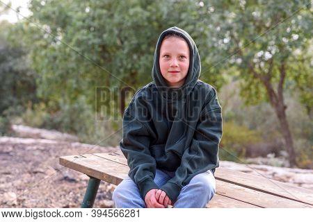 Tween Girl In A Hoodie. Portrait Of A Pensive Dreamer Teenage Girl Wearing Green Hoodie Sitting On T