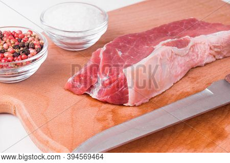 Piece Of Light Fresh Raw Beef On Wooden Board With Salt And Peppercorns In Bowls