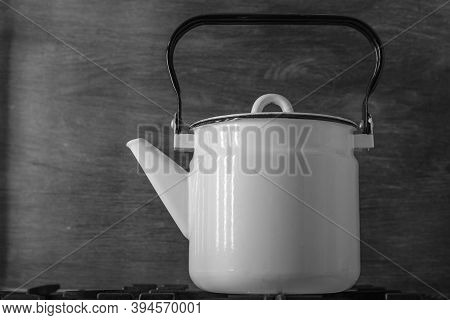 White Enameled Vintage Teapot Stands On A Stove, On A Black Background - Closeup