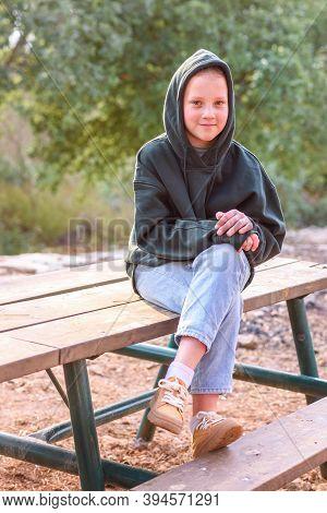 Tween Girl In A Hoodie. Portrait Of A Smiling Teenage Girl Wearing Green Hoodie, Jeans And Yellow Bo