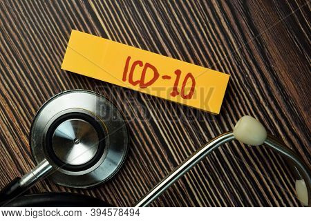 Icd - 10 Write On Sticky Note And Stethoscope Isolated On Wooden Table. Medical Concept