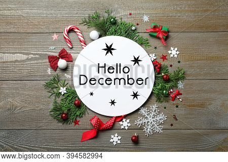 Greeting Card With Text Hello December, Fir Tree Branches And Christmas Decor On Wooden Background,