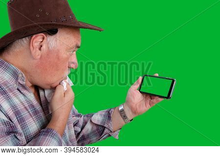 An Elderly Rancher Wearing A Brown Hat Checkered Shirt Staring In Confusion At A Green Screen On A S