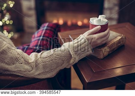 Woman Hand With Old Retro Book And Cup Of Hot Cocoa And Marshmallow On Wooden Table Near Christmas T