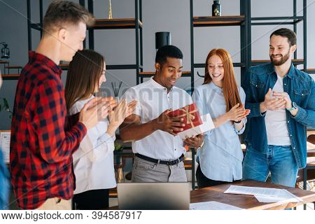 Happy Team Of Multi-ethnic Business People Congratulate African-american Colleague And Give Gift Wit