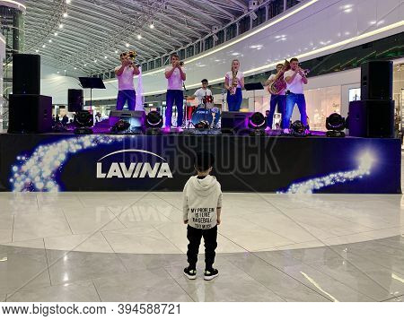 A Child At A Concert Of An Instrumental Ensemble. The Boy Stands On Against The Stage. Concert Of A